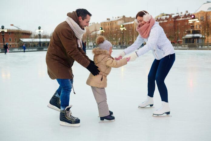 Młodzi rodzice uczący dziecko jazdy na łyżwach